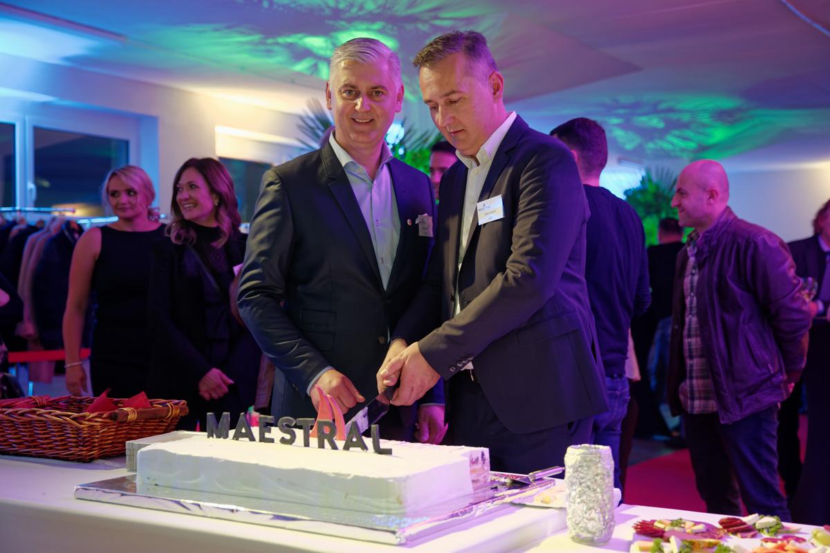 Lujo i Jozo Luburić režu tradicionalnu tortu ukrašenu logom tvrtke.